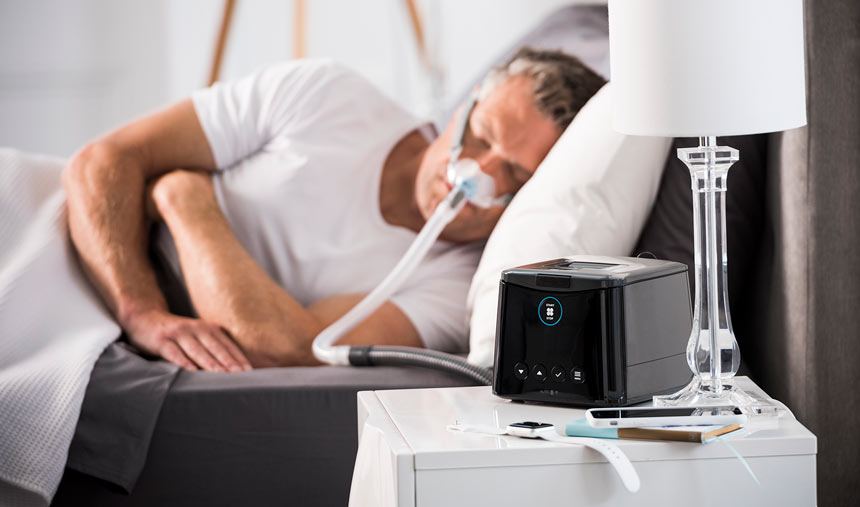 Man sleeps wearing an Eson2 Nasal Sleep Apnea Mask with F&P Sleepstyle on the bedside table