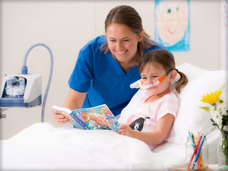 Nurse and child reading in hospital bed with F&P Airvo in background