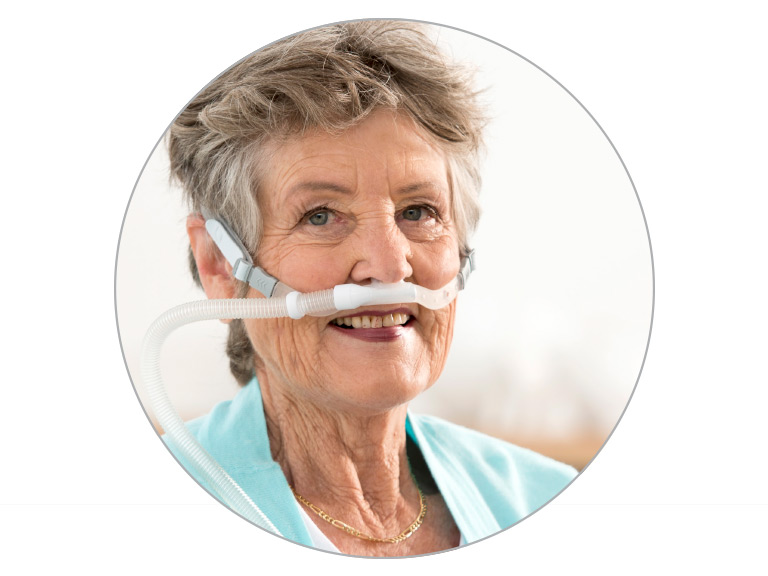 Woman smiles while wearing F&P Optiflow S3 Nasal Cannula