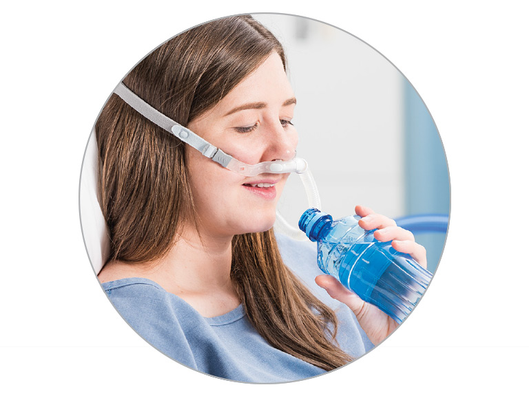 Woman drinks from water bottle while wearing F&P Optiflow 3S Nasal Cannula
